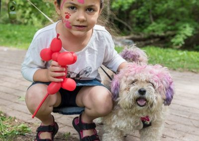 Little girl with painted face and her puppy dog with pink hair